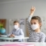 Child with face mask back at school after covid-19 quarantine and lockdown